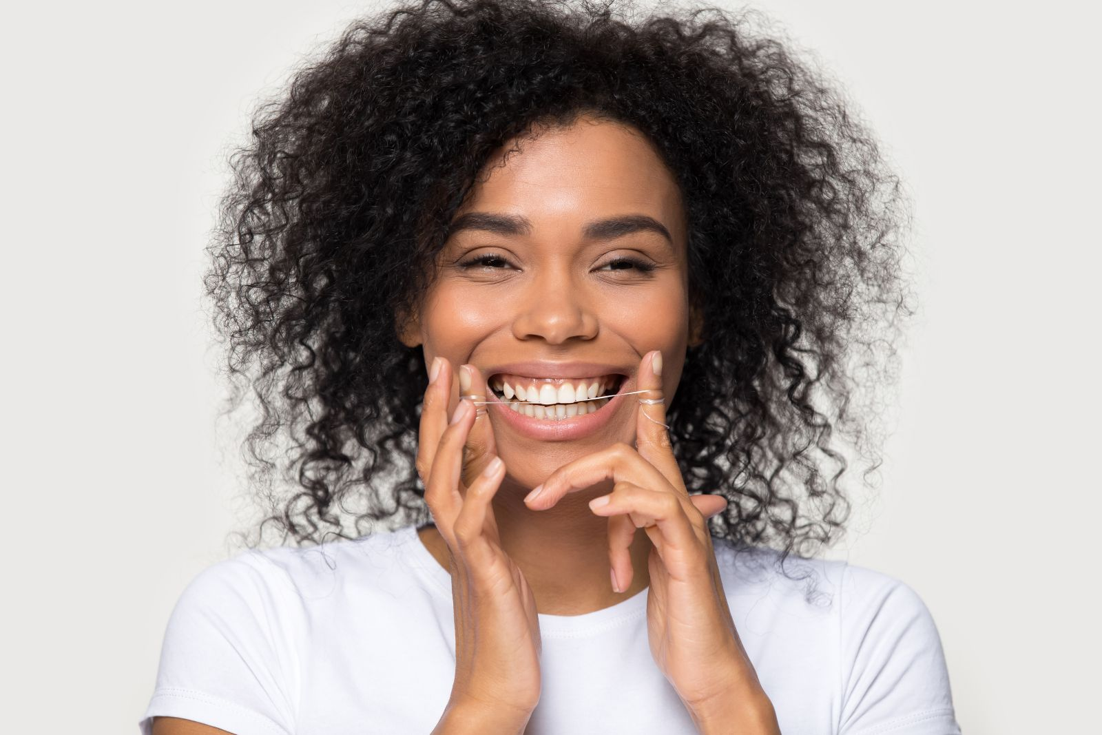 Closeup portrait happy african woman cleaning teeth with dental floss